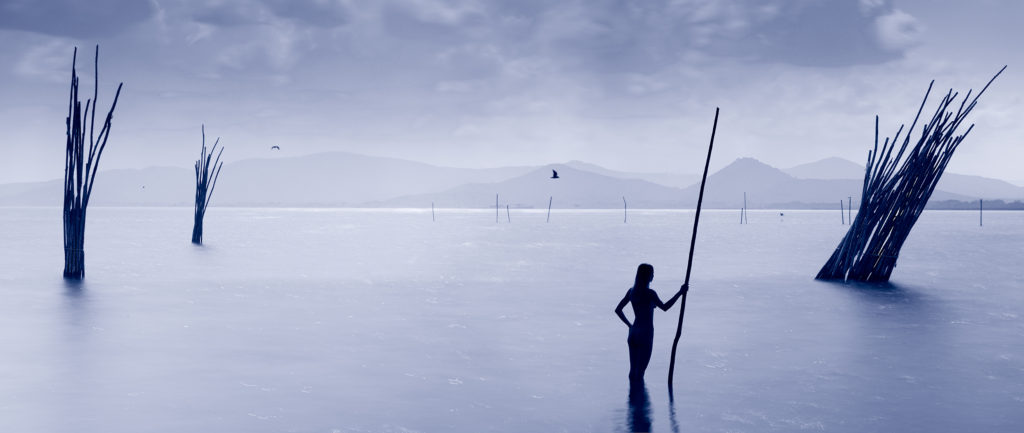Water portrait- woman with pole, a water statue in lake Trasimeno
